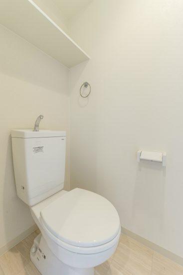 名古屋市中川区の賃貸マンションの白で統一された棚付きトイレ