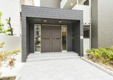 名古屋市中区の賃貸マンションの植栽が両側にある玄関アプローチと高級感あるエントランス