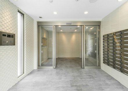 名古屋市中区のワンルーム賃貸マンションの白いエンボス加工の壁がおしゃれなメールボックス付きエントランスホール
