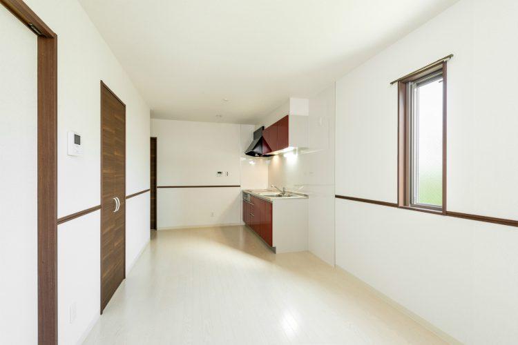 愛知県春日井市のメゾネット賃貸アパートの赤色のキッチンが映えるLDK