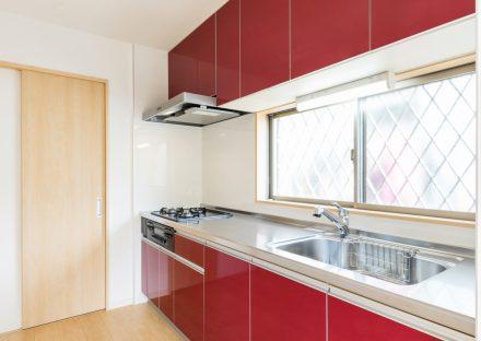 名古屋市名東区の戸建賃貸住宅の目の前に窓があり、明るい赤色のシステムキッチン