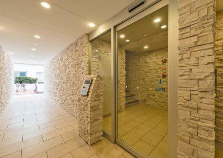 名古屋市千種区の賃貸マンションのナチュラルカラーで凹凸のある石調の壁のエントランス