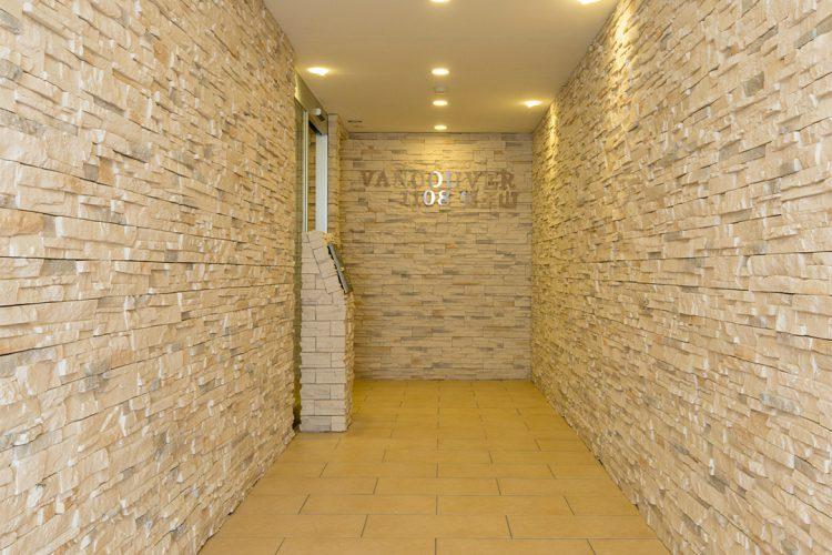 名古屋市千種区の賃貸マンションのナチュラルカラーの石調の壁に囲まれたエントランス
