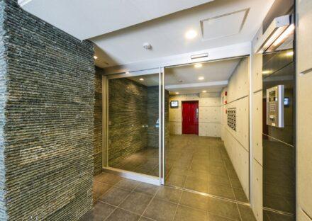 名古屋市名東区の賃貸マンションの赤のエレベータの扉が目を引くエントランスホール