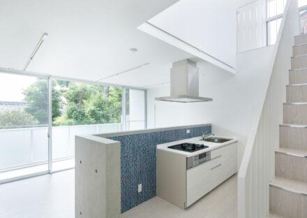 名古屋市天白区の賃貸マンションの白にオープンキッチン裏の青いタイルが映えるLDK