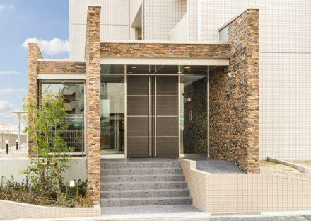 名古屋市名東区の賃貸マンションの凹凸のある石壁と植栽のあるエントランス