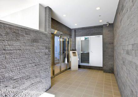 名古屋市名東区の賃貸マンションの高級感ある凹凸のある壁のエントランス