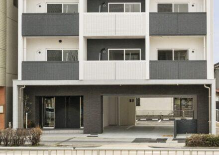 名古屋市瑞穂区の賃貸マンションの駐車場が奥にあるモノトーンの外観デザイン