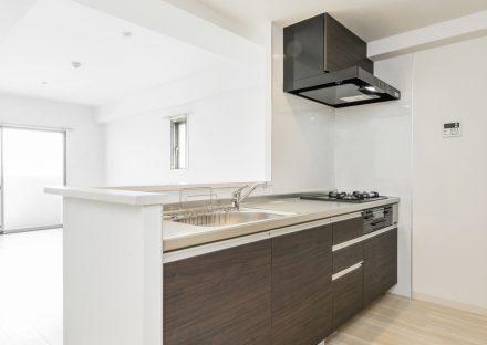 名古屋市名東区の賃貸マンションの白い部屋に映えるダークブラウンのオープンキッチン