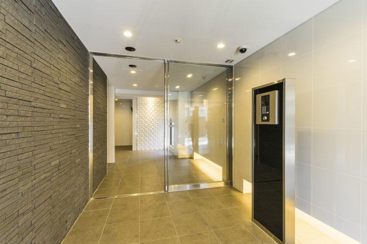 名古屋市中村区の賃貸マンションの光沢のある壁と間接照明で照らされたエントランスホール
