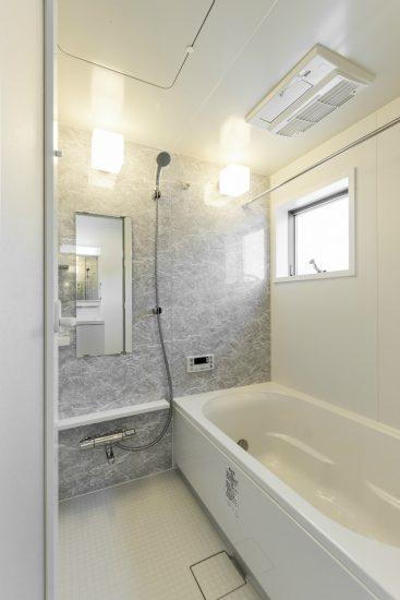 名古屋市北区のメゾネット賃貸アパートの白っぽい大理石柄の壁のあるお風呂場