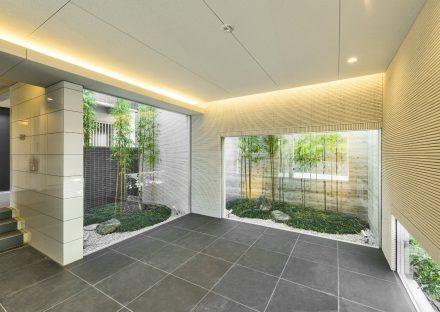 名古屋市名東区の賃貸マンションのガラスの奥に庭が見えるエントランスホール