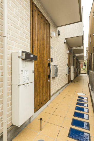 名古屋市緑区のロフト付きメゾネット賃貸の木の玄関ドアがおしゃれな通路