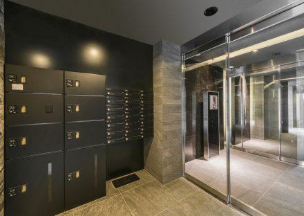 名古屋市中区の賃貸マンションの黒色の高級感ある宅配・ポストボックス付きのエントランスホール写真