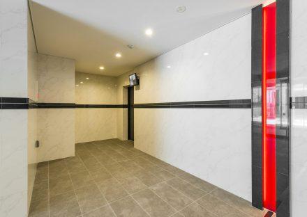 名古屋市千種区の賃貸マンションの赤いラインが目を引くデザインのエレベーターホール