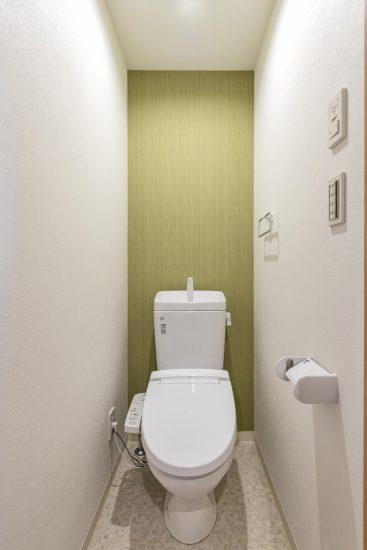 名古屋市中村区の木造3階建賃貸アパートの緑のアクセントクロスが映えるトイレ
