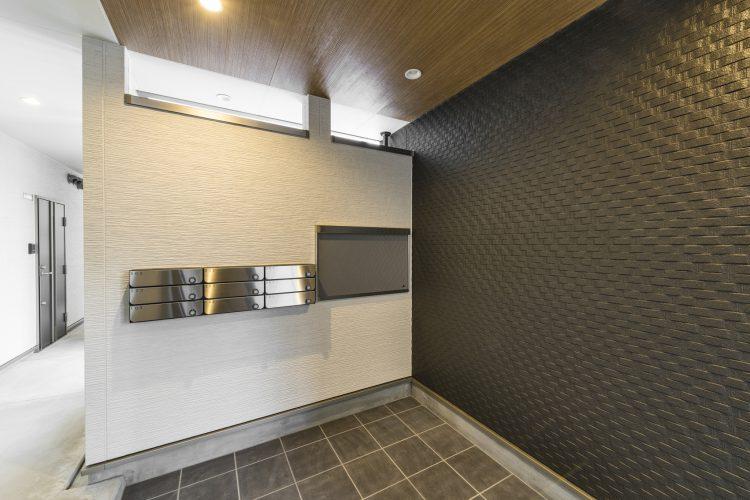 名古屋市中村区の木造3階建賃貸アパートの凹凸のある黒い壁がおしゃれなエントランスホール