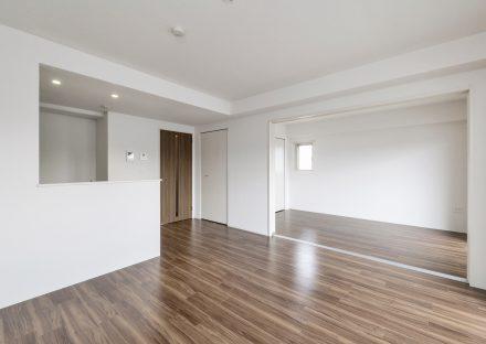 名古屋市名東区の賃貸マンションの木目調のフローリングがアクセントのリビングダイニングと洋室
