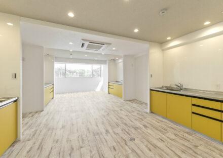 愛知県日進市の学生寮の黄色が映える共用システムキッチン