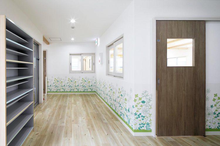 名古屋市天白区の保育施設の植物の絵の描かれた壁のある下駄箱の付いた玄関ホール