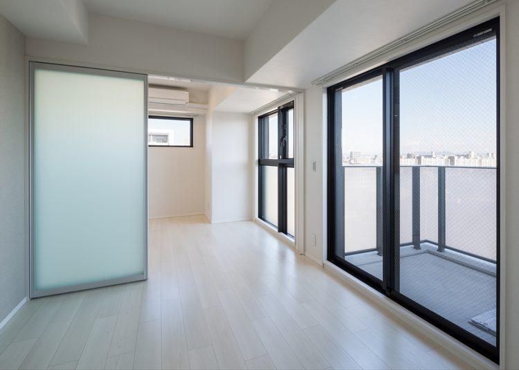 名古屋市北区のモダンな10階建賃貸マンションのバルコニー付き半透明のドアとパネルで明るい洋室