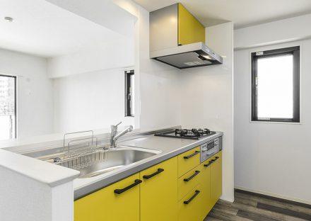 名古屋市名東区の賃貸マンションの黄色のオープンキッチン写真