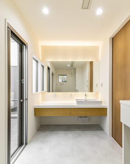 名古屋市北区の注文住宅の大きな鏡の付いた明るいの洗面台の写真