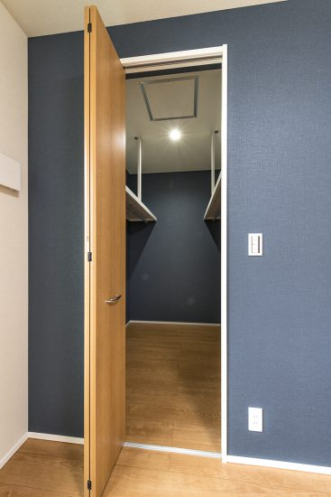 名古屋市北区の注文住宅のネイビーの壁がおしゃれな大容量のウォークインクローゼットの写真