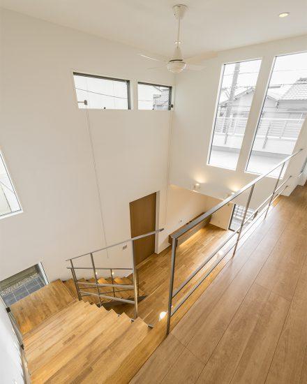 名古屋市北区の注文住宅のシーリングファン付きの光が入る大きな窓がある吹き抜けと明るい階段