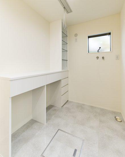 名古屋市北区の注文住宅の白で統一された収納付きの脱衣所の写真