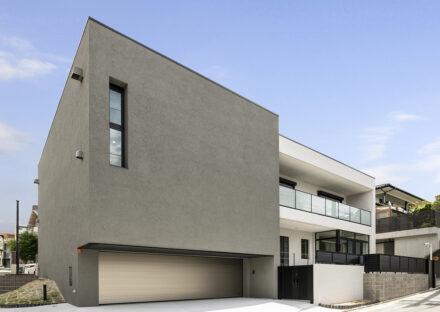 名古屋市昭和区の注文住宅の広いインナーガレージの付いたシンプルな外観デザインの新築写真