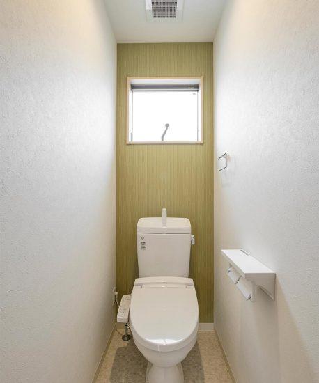 アクセントカラーがグリーンの窓付きの明るいトイレ