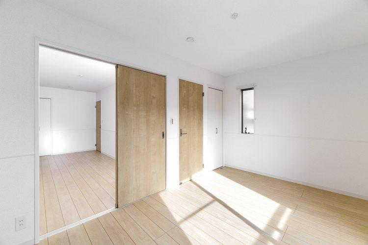 名古屋市名東区の戸建賃貸住宅の木目のドアと床がナチュラルテイストの洋室の新築写真