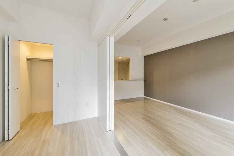 名古屋市中村区の賃貸マンションのウォークインクローゼット付きの洋室とリビングダイニングの新築写真