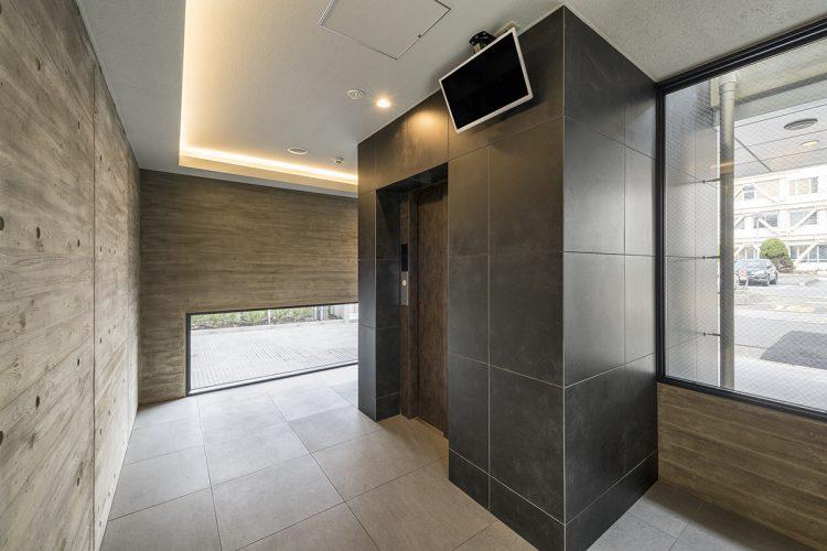 名古屋市中川区の賃貸マンションの大判タイルで高級感があり、地窓で明るいエレベーターホールの新築写真