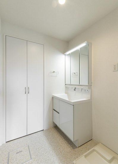 名古屋市中村区の賃貸マンションの白で統一された棚が横にある洗面台の新築写真