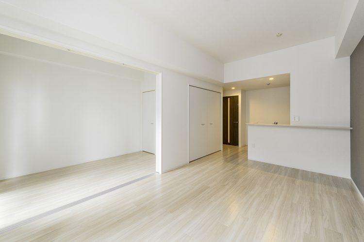 名古屋市中村区の賃貸マンションの白を基調としたリビングダイニングと洋室の新築写真