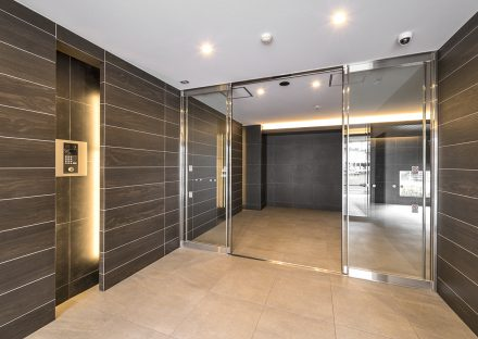 名古屋市中川区の賃貸マンションのダークの色合いのエントランスホールの新築写真