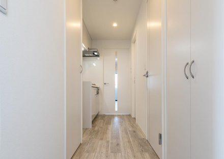 名古屋市中川区の賃貸マンションの収納の付いた玄関とキッチンの新築写真