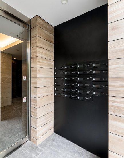 名古屋市中区の賃貸マンションの木目の壁に映えるブラックのメールボックス