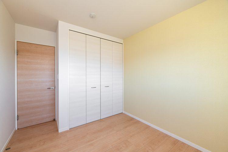 名古屋市名東区のシンプルなデザインの注文住宅の温かみのある色合いの洋室