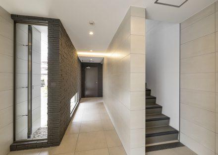 名古屋市名東区の3階建て賃貸マンションの凹凸のある壁と地窓の付きの高級感あるエントランスホール