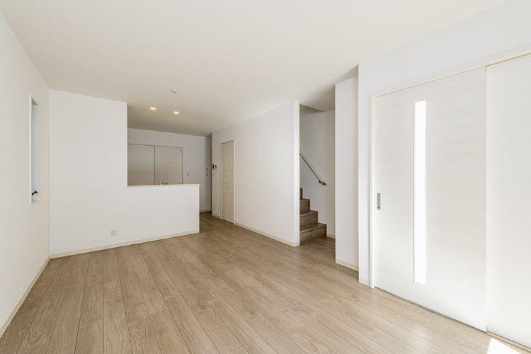 名古屋市西区のモダンな戸建賃貸住宅の白い壁と落ち着いた色のフローリングのLDK