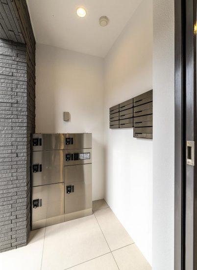 名古屋市名東区の3階建て賃貸マンションのメタリックな宅配ボックスとメールボックス