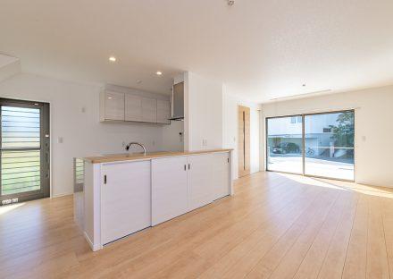名古屋市名東区のシンプルなデザインの注文住宅のキッチンの裏に引き戸収納と吊戸棚のあるLDK