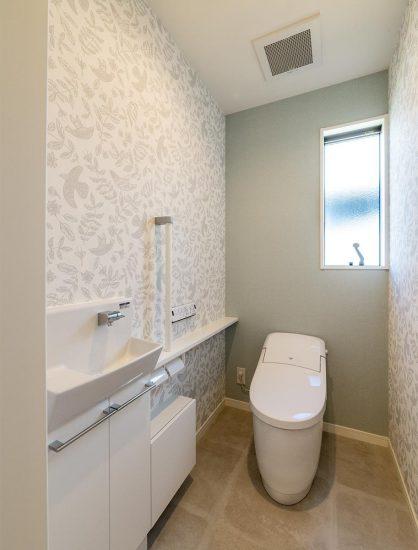 名古屋市名東区のシンプルなデザインの注文住宅のおしゃれな壁紙の手洗い付きトイレ