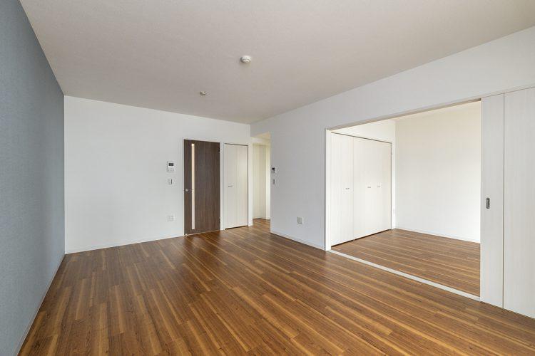 名古屋市名東区の3階建て賃貸マンションのアクセントカラーの壁のあるLDKと収納付きの洋室