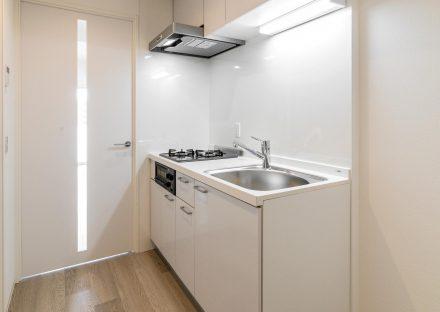 愛知県小牧市のレトロとモダンを組み合わせたデザインの賃貸マンションのガスコンロ付きのコンパクトなシステムキッチン