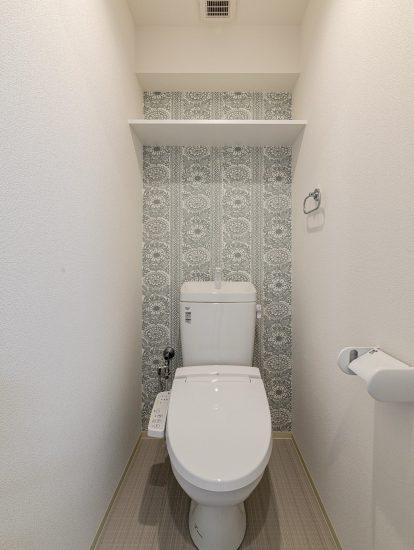 愛知県小牧市のレトロとモダンを組み合わせたデザインの賃貸マンションの棚の付いたモダンな壁紙のトイレ