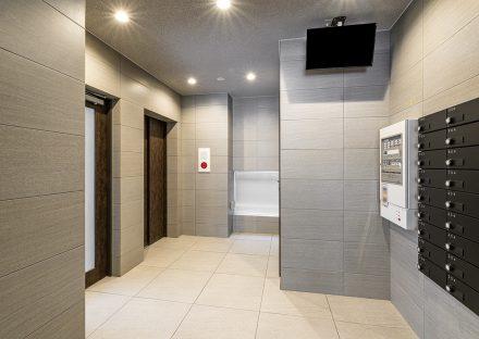 愛知県小牧市のレトロとモダンを組み合わせたデザインの賃貸マンションの黒色のメールボックスの付いたエレベーターホール